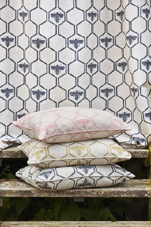 Barneby Gates -  Barneby Gates Fabric Collection - Bees and hexagons printed in dark blue, light pink and green-gold on a cream coloured fabric backdrop, as well as three cushions