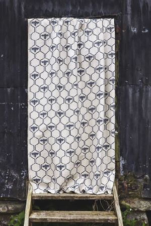 Barneby Gates -  Barneby Gates Fabric Collection - Cream coloured fabric with dark blue hexagons and bees printed repeatedly over it, hanging above some rustic wooden steps