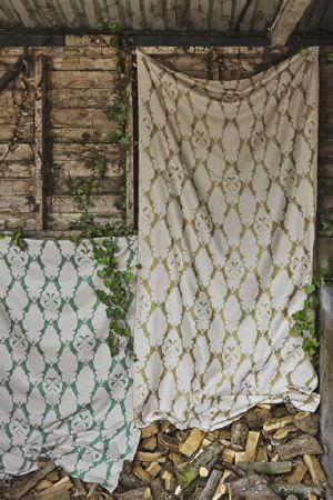 Barneby Gates -  Barneby Gates Fabric Collection - Ornate white patterns printed as a large, repeated pattern over hanging swathes of green and gold coloured fabrics