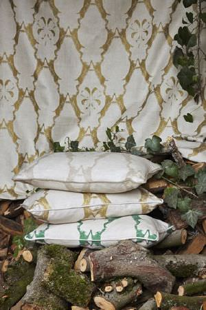 Barneby Gates -  Barneby Gates Fabric Collection - Stack of 3 cushions in green, gold and silver, in front of a gold fabric backdrop, all printed with a large, repeated, ornate white pattern