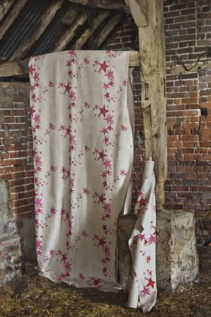 Barneby Gates -  Barneby Gates Fabric Collection - A bolt and a length of fabric hanging from a wooden beam - both are cream in colour and have red-pink stars arranged in circular shapes