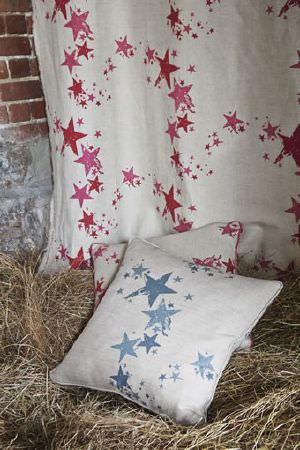 Barneby Gates -  Barneby Gates Fabric Collection - Blue stars printed on a cream coloured cushion, with a cream coloured cushion with red and pink stars and a matching sample of fabric