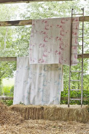 Barneby Gates -  Barneby Gates Fabric Collection - Wooden ladder beside two hanging lengths of butterfly print fabric, both in cream, but one with a blue design and one with a pink design