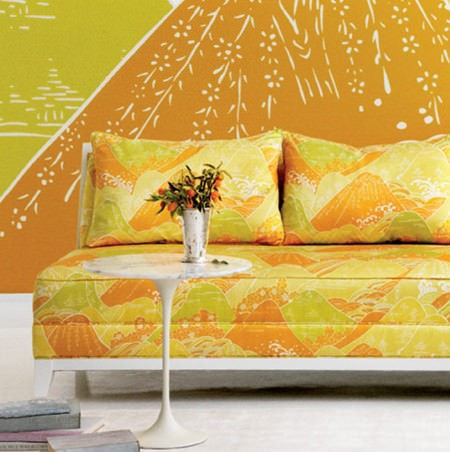Beacon Hill -  Floating World Silks Fabric Collection - Orange and yellow abstract printed sofa seat and back cushions, with a white table, a silver vase, and orange and mustard walls