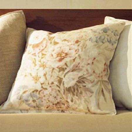 Blithfield -  Collection II Fabric Collection - A dark brown and caramel coloured seat with three plain and floral cushions in shades of cream, light brown and white