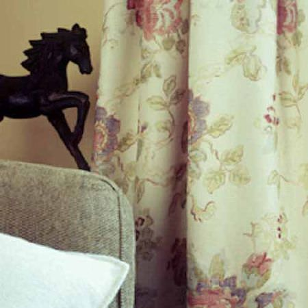 Blithfield -  Collection II Fabric Collection - A black horse statue, a grey sofa, a white cushion and floral curtains made in light shades of cream, pink, purple and green
