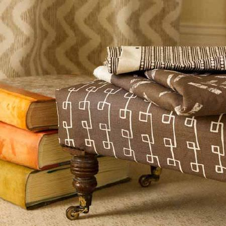 Blithfield -  Collection III Fabric Collection - A stack of three books with a low dark brown and white padded footstool, with 2 folds of patterned fabrics, and curtains