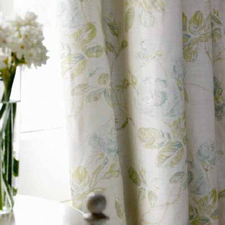 Blithfield -  Collection III Fabric Collection - A glass vase with white flowers beside long curtains with a printed leaf design in white, pale blue and olive green