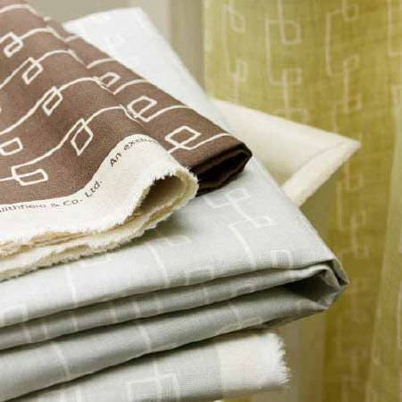 Blithfield -  Collection III Fabric Collection - Neatly folded fabrics and curtains with angular swirling patterns in white, apple green, chocolate brown and pale blue-grey