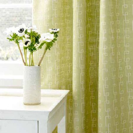 Blithfield -  Collection III Fabric Collection - A simple white design on light green coloured curtains, beside a white wooden table, with a white vase holding flowers