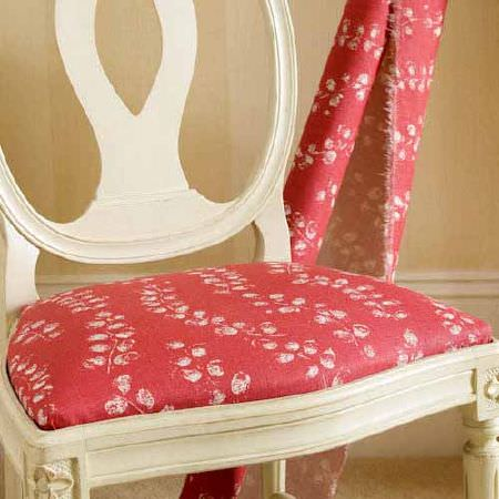 Blithfield -  Collection III Fabric Collection - An elegant off-white painted wooden chair with a seat covered in floral white and raspberry fabric, beside a fabric bolt