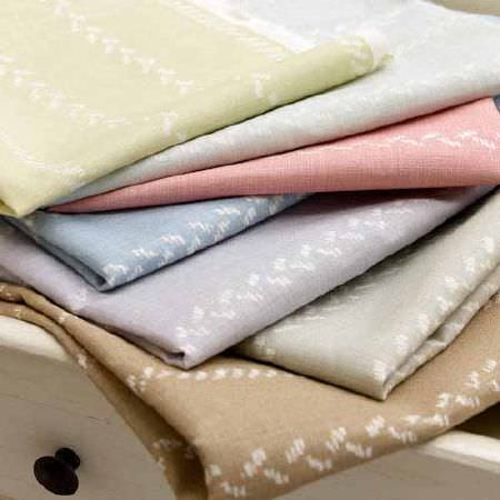 Blithfield -  Collection III Fabric Collection - A drawer with a stack of 7 subtly patterned fabrics, made in pastel shades of brown, grey, mauve, blue, pink and green