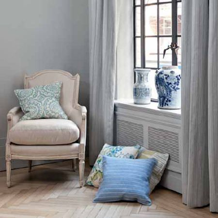 Blithfield -  Collection V Fabric Collection - An ivory padded and wood armchair with four patterned and striped cushions in shades of blue, beside grey curtains