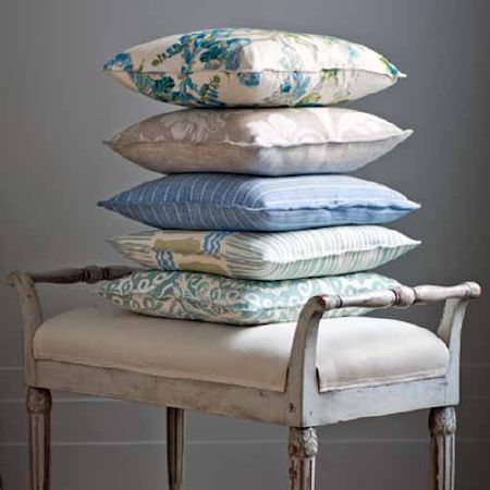 Blithfield -  Collection V Fabric Collection - A stack of 5 floral and patterned cushions printed in shades of cream, blue and green, on an off-white padded wooden bench