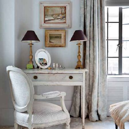 Blithfield -  Collection V Fabric Collection - A distressed white wood side table with a padded white armchair, with grey curtains, a mirror, and gold and black lamps