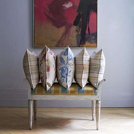Blithfield -  Langham Fabric Collection - Five blue, red and cream patterned and floral cushions, stacked on a white wooden bench with a striped green and blue seat