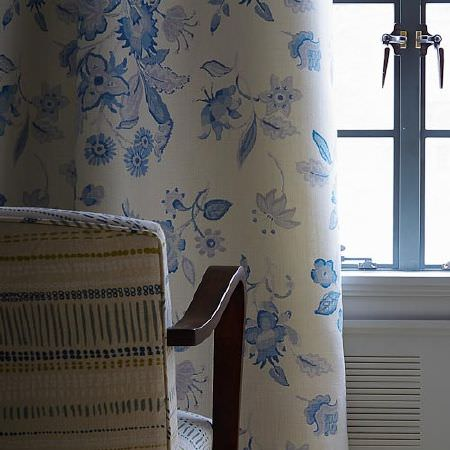 Blithfield -  Langham Fabric Collection - Blue and white floral curtains behind a padded chair with dark wood arms, covered in cream, blue and green patterned fabric