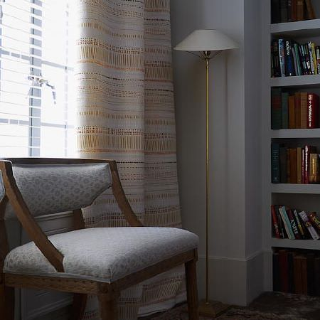 Blithfield -  Langham Fabric Collection - Gold and white patterned curtains, a gold floor lamp with a white shade, and a light grey and white wooden framed armchair