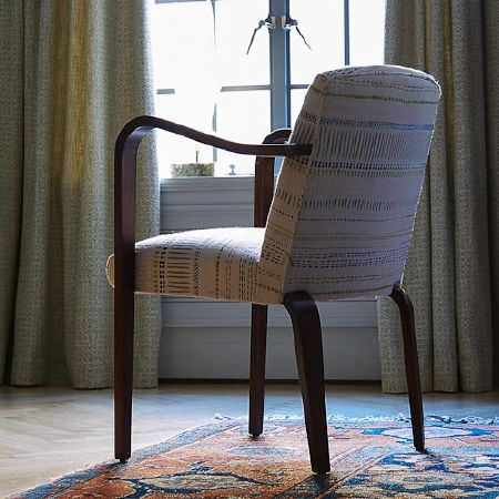Blithfield -  Langham Fabric Collection - Grey and white patterned curtains, a white, blue and green patterned chair with dark wood arms and legs, and a dark rug