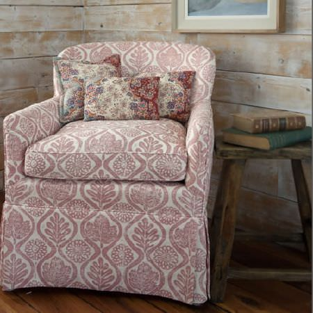 Blithfield -  Peggy Angus Fabric Collection - Armchair covered with pale pink and white printed leaf designs, with a rustic wooden table, andred and white scatter cushions
