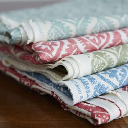 Blithfield -  Peggy Angus Fabric Collection - Five folds of patterned fabric, each in white, with designs in red, sky blue, dove  grey, cherry and powder blue