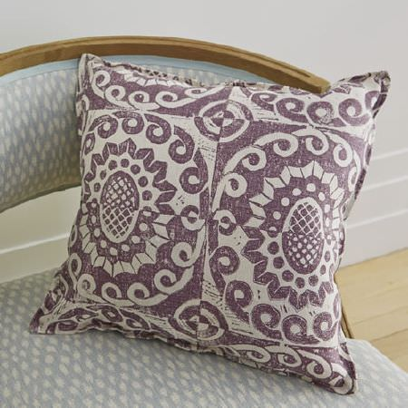 Blithfield -  Peggy Angus Fabric Collection - A cushion and a wooden framed armchair, both covered with different patterned fabrics in white, pale blue and dark purple