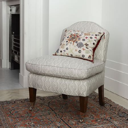 Blithfield -  Peggy Angus Fabric Collection - A pale grey and white patterned chair with dark wood legs, on a dark rug, with a cushion in white, navy, red and grey
