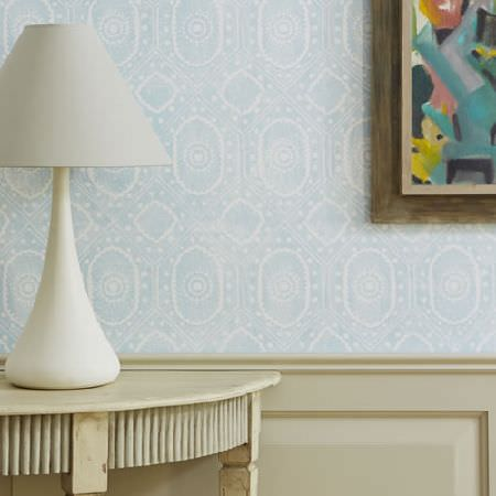 Blithfield -  Somerton Fabric Collection - A simple white lamp on a light cream semi-circular table, against a panelled wall with blue and white patterned wallpaper