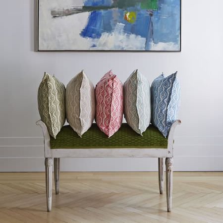 Blithfield -  Somerton Fabric Collection - A white wooden framed bench with a forest green seat, beneath a row of green, grey, red, blue and white patterned cushions