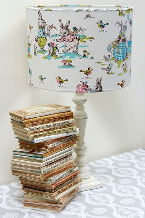 Charlotte Gaisford -  Nursery Fabric Collection - White lamp decorated with a colourful pattern of cartoon animals on an elegant grey tablecloth