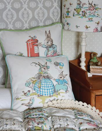 Charlotte Gaisford -  Nursery Fabric Collection - Matching design featuring bunnies on white lamp, a set of white cushions and a white bed cover