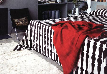 Christopher Farr -  Printed Indoor Fabric Collection - A white rug beside a black chair and a bed with a black and white candlestick print pattern and a bright red throw