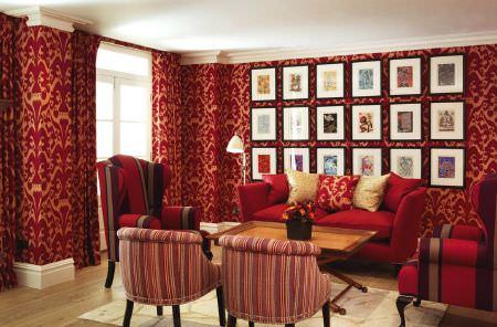 Christopher Farr -  Printed Indoor Fabric Collection - Ornate red and gold walls with a red armchair and four redstriped armchairs, with a wooden table and scatter cushions