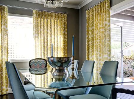 Christopher Farr -  Printed Indoor Fabric Collection - Clear perspex table withsix plain pale blue chairs, one patterned chair, green and white curtains, a bowl and candlesticks