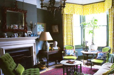 Christopher Farr -  Printed Indoor Fabric Collection - A grass green sofa and armchairs with patterned cushions, yellow curtains and a pelmet, wooden tables, a lamp and a mirror