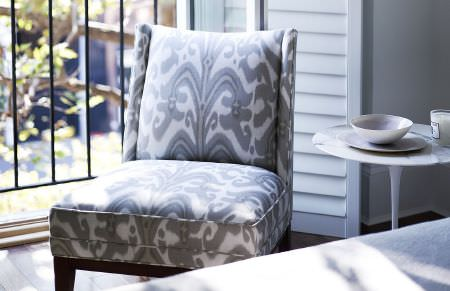 Christopher Farr -  Printed Indoor Fabric Collection - A grey and white patterned padded chair made with dark wood legs, beside a small round white table and white bowls