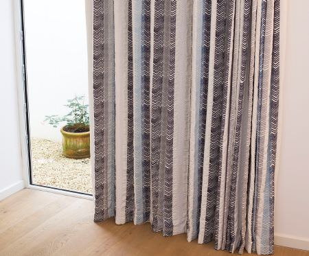 Christopher Farr -  Printed Indoor Fabric Collection - A yellow-green cylindrical flower pot, near floor-length curtains with a patterned striped design in cream and grey shades