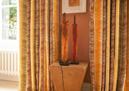 Christopher Farr -  Printed Indoor Fabric Collection - A wooden plinth, orange sculptures, long curtains with a patterned striped design in shades of orange, cream and brown