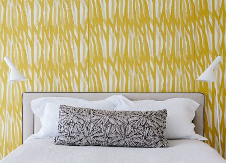 Christopher Farr -  Printed Indoor Fabric Collection - White and mustard yellow wallpaper with a small light grey headboard, white bedding, two white lamps and a grey cushion