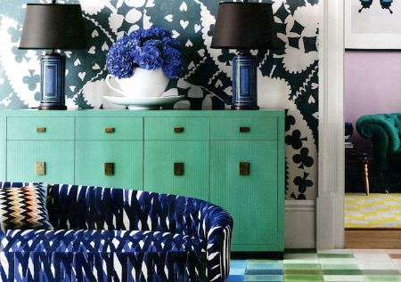 Christopher Farr -  Printed Indoor Fabric Collection - A mint green side table with two dark blue and black lamps, an oversized white teacup vase and a blue and black patterned sofa