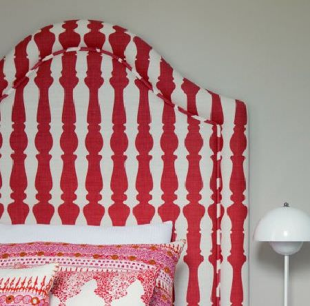 Christopher Farr -  Printed Indoor Fabric Collection - A red and white candlestick patterned headboard with red, pink and white ornately patterned cushions, beside a white lamp