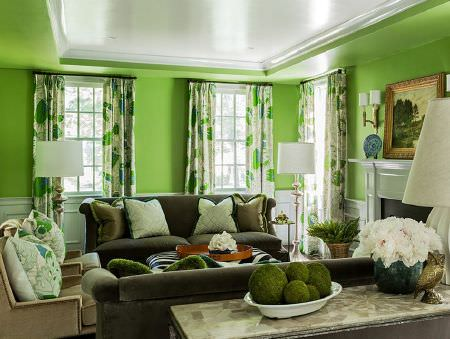 Christopher Farr -  Printed Indoor Fabric Collection - Green and grey leaf patterned curtains with dark grey sofas, beige armchairs, plain and patterned cushions and white lamps