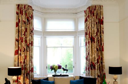 Christopher Farr -  Printed Indoor Fabric Collection - A beige sofa with plain dark cushions,black and cream lamps and curtains featuring a large design in beige, cream and red