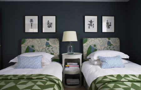 Christopher Farr -  Printed Indoor Fabric Collection - Grey and green patterned headboards to plain white beds with geometric print throws and light blue cushions, with a lamp