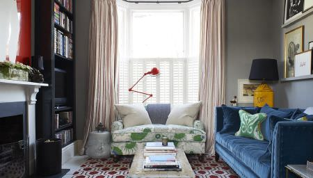 Christopher Farr -  Printed Indoor Fabric Collection - Sofas in green andgrey patterns and plain blue, with various scatter cushions,a coffee table, and red, yellow and grey lamps