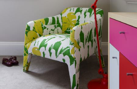 Christopher Farr -  Printed Indoor Fabric Collection - A small green and white parrot print chair with ared anglepoise floor lamp andcupboards made in red, pink and white