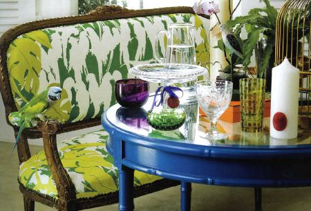 Christopher Farr -  Printed Indoor Fabric Collection - A green bird perched on a wood framed green and white padded sofa, with a round bright blue table with various glassware