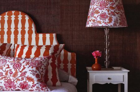 Christopher Farr -  Printed Indoor Fabric Collection - Orange, red and white candlestick prints covering a headboard and cushion, with a patterned cushion and lampshade