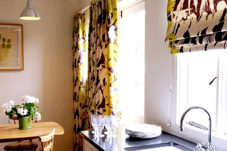 Christopher Farr -  Printed Indoor Fabric Collection - Purple, green and white patterned curtains and blinds beside a wooden table and chair,with glasses, crockery and a green vase