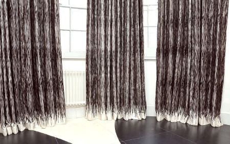 Christopher Farr -  Printed Indoor Fabric Collection - Three floor-length curtains made with dark grey patterns fading to white at the bottom, touching a black and white floor